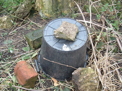 Photo of an upturned bucket surrounded by a few broken bricks and one on top