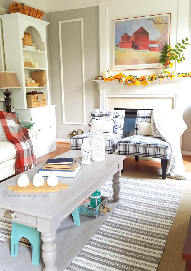 turned leg coffee table with white pear trio, plaid chairs and throw blanket, striped rug, bookcase
