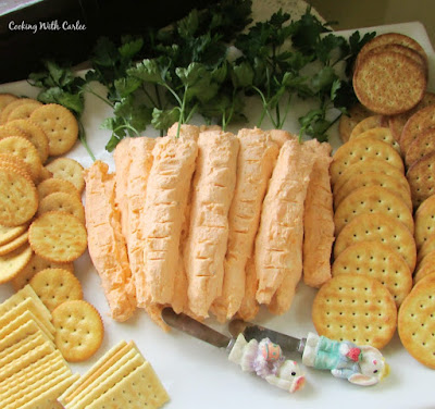 platter of carrot shaped cheese balls with easter bunny spreader knives and crackers