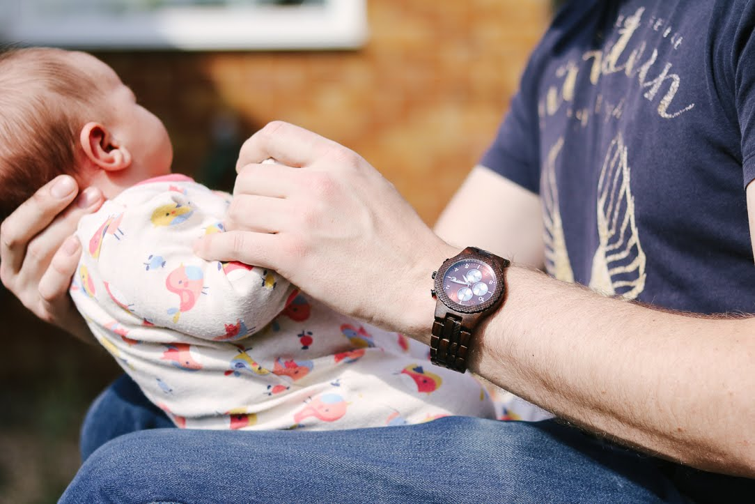 a close up of a man's hands side on holding a newborn baby. The man is wearing blue jeans, a navy shirt and a dark wooden watch