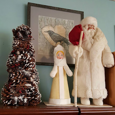 Ukrainian Grandfather Frost and Snow Maiden beside a tree made of pine cones