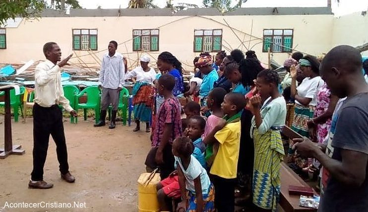 Pastor predicando en escombros de iglesia en Mozambique
