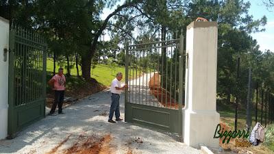 Execução das guias de pedra para executar a rua de pedra com pedrisco em entrada da fazenda em Atibaia-SP com os pilares do portão e o portão de ferro. Na foto, Bizzarri examinando os detalhes e no paisagismo o gramado com grama batatais.