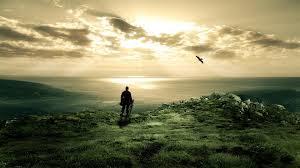 Οδοιπόρος σε βουνό, κοιτάζει τη θάλασσα. Ακολουθεί το κείμενο: Δε θέλω εγώ τριαντάφυλλα στον έρημό μου δρόμο, δέντρο δεν θέλω να σταθώ, πηγή να ξεδιψάσω. Eγώ ανεβαίνω το βουνό, μ' ένα σταυρό στον ώμο. Tου φθινοπώρου ας απλωθούν τα φύλλα, να περάσω.