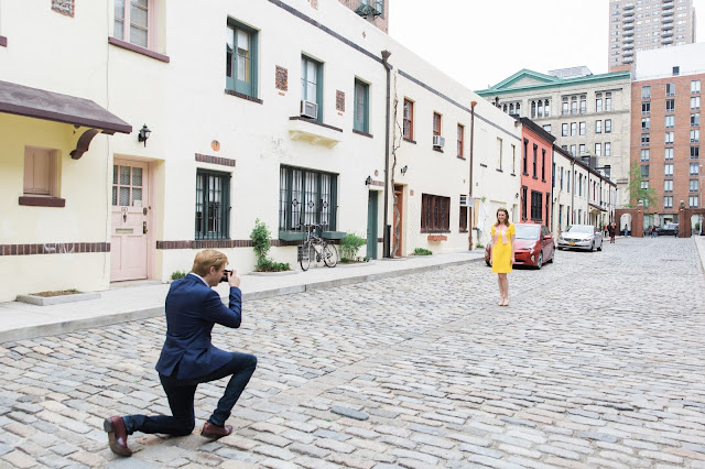 Ted kneels to take a photo of Liz in a Yellow dress on the cobblestone street