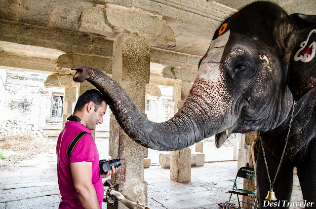 tourist at the sacred center of hampi temple blessed by elephant