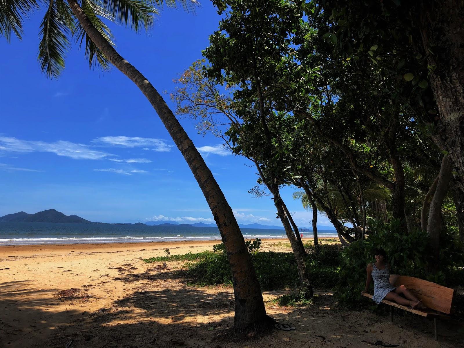 Plaża w australijskim miasteczku Mission Beach z drewnianą ławeczką, na której półsiedzi podróżniczka pod gęstą roślinności lasu deszczowego.