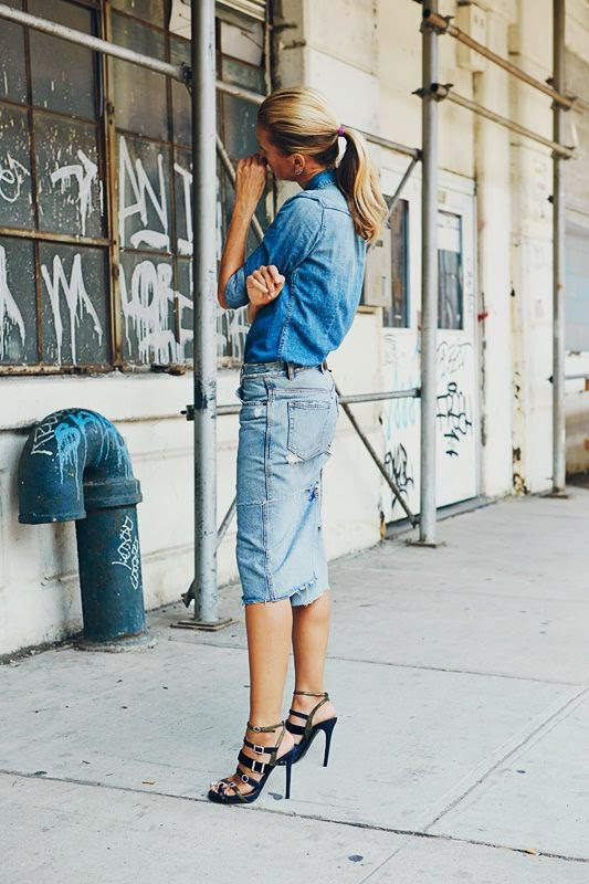 a woman with jeans skirt and chambray shirt with high jeels