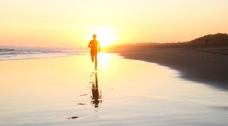 menino correndo na praia no por do sol