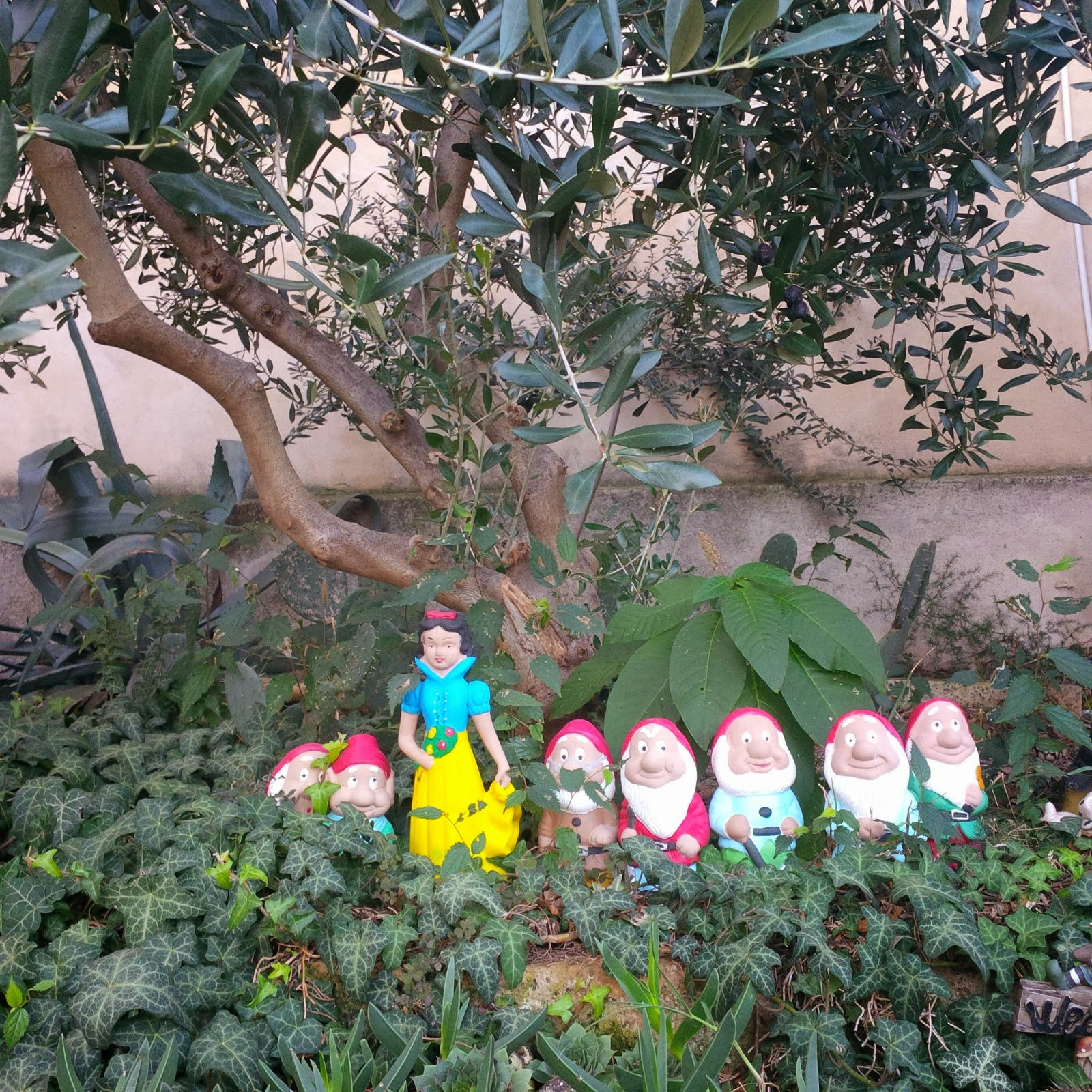Disney figurines under an olive tree in the garden of a cafe in Arqua Petrarca