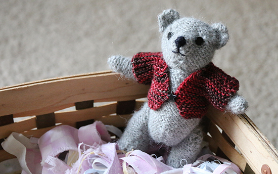 Hand Knit Wool Teddy Bear Resting Against the Side of a Basket