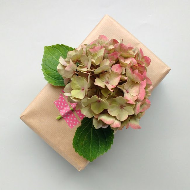 brown paper parcel with a hydrangea bloom as a gift topper
