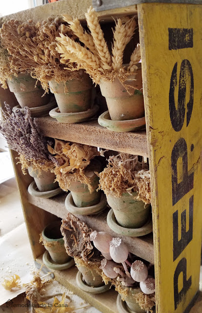 Yellow Pepsi soda crate repurposed with dried flowers in terracotta pots