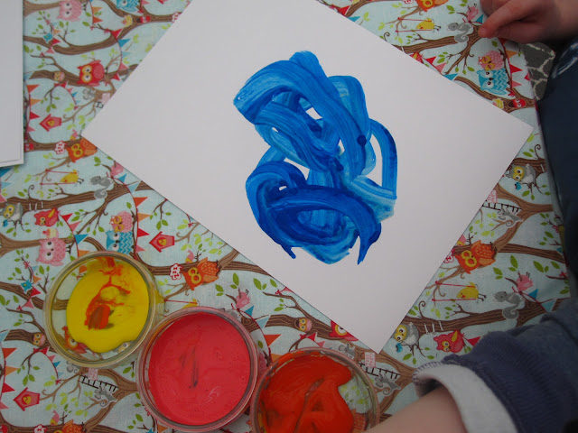 A toddler painting the card