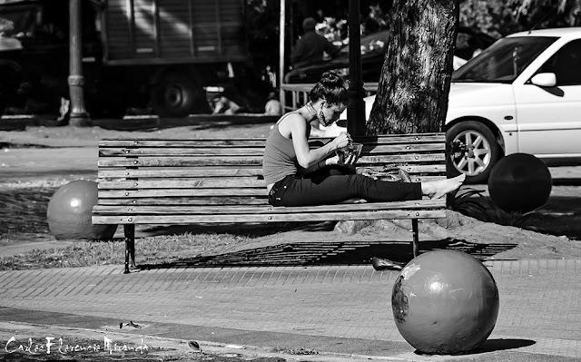 Chica en un banco de plaza comiendo una ensalada.Blanco y Negro