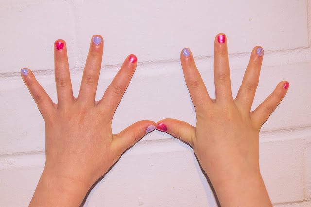Little hands against a white brick wall, the nails are painted blue and pink