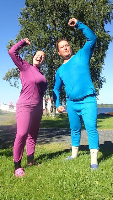 Mies ja nainen värikkäissä pitkissä kerrastoissa poseeraa nurmikolla