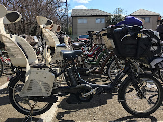 A picture of a parking lot full of mama-chari bicycles next to a local kindergarten. Most have one or two child seats and are power-assisted.