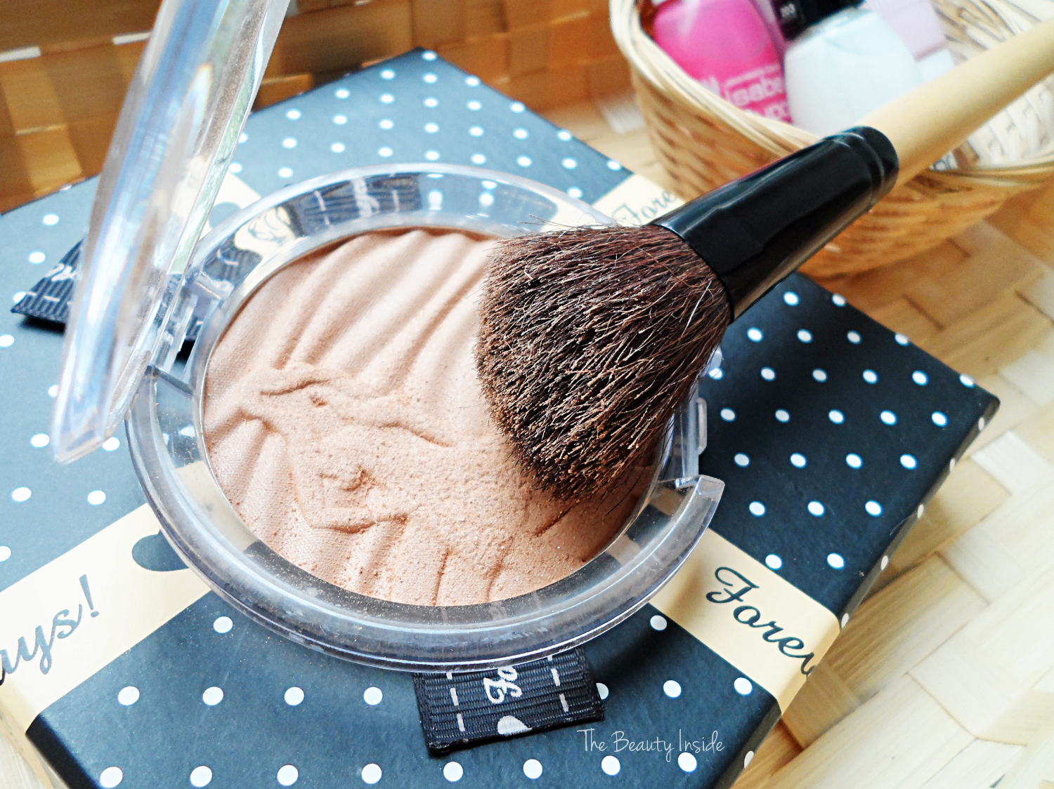 an opened bronzing powder by essence with a face brush