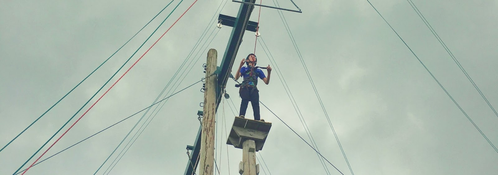 A 13 year old boy stands atop a small platform high in the air. He is connected to a rope and wearing a helmet. His hands are reaching forward as he prepares to jump to a handrail hanging in the air.