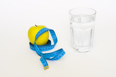 Apple and tape measure next to water glass
