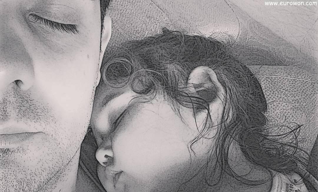 Padre e hija durmiendo una siesta dominical en el sofá