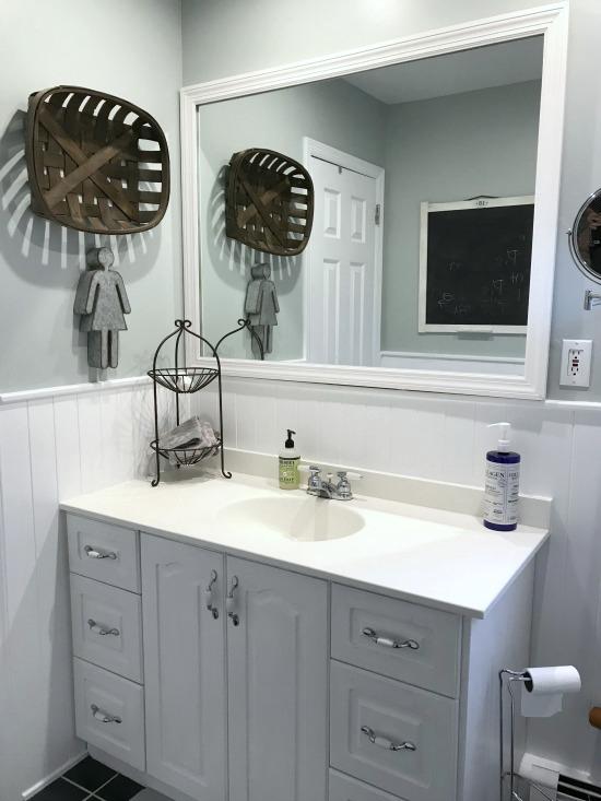Framed mirror and white vanity in bathroom