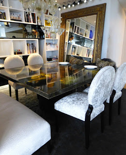 Gorgeous Upholstered Dining Chairs under Transparent Chandeliers near the Wide Wood Framed Mirror on the Wall