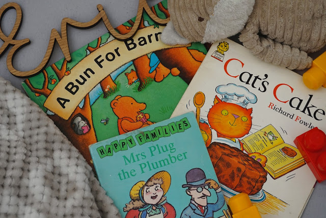 flat lay photograph of a selection of children's books, toys and a carved wooden name sign