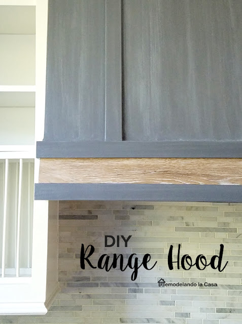 GREy and wooden tone range hood in white kitchen