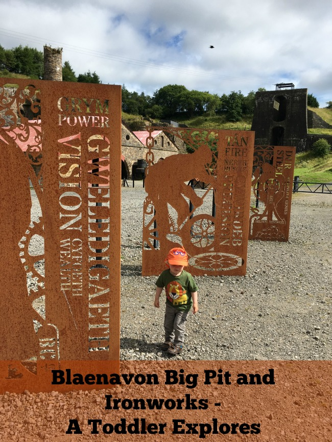 Blaenavon-Big-Pit-and-Ironworks-A-Toddler-Explores-text-on-picture-of-toddler-next-to-ironwork-panels