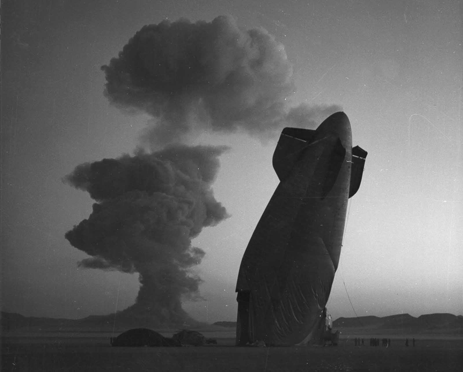 The tail section of a U.S. Navy blimp is shown with the Stokes cloud in the background at the Nevada Test Site on August 7, 1957. The blimp was in temporary free flight in excess of five miles from ground zero when it was collapsed by the shock wave from the blast. The airship was unmanned and was used in a military effects experiment.