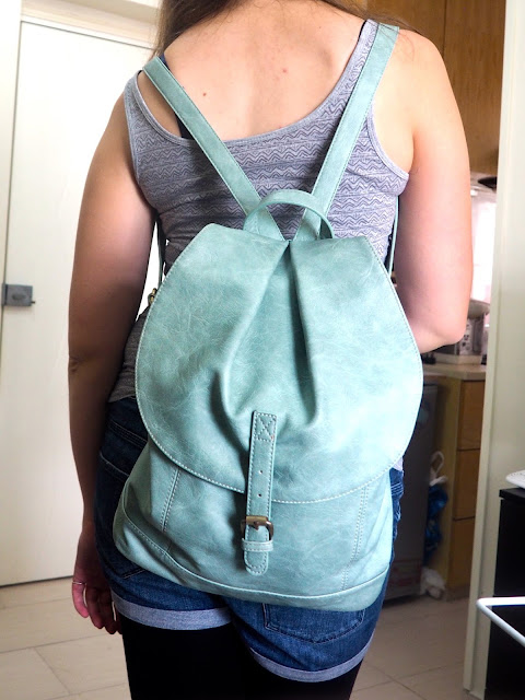 Hiking | outfit details from the back, of mint green leather effect backpack, with drawstring and flap close