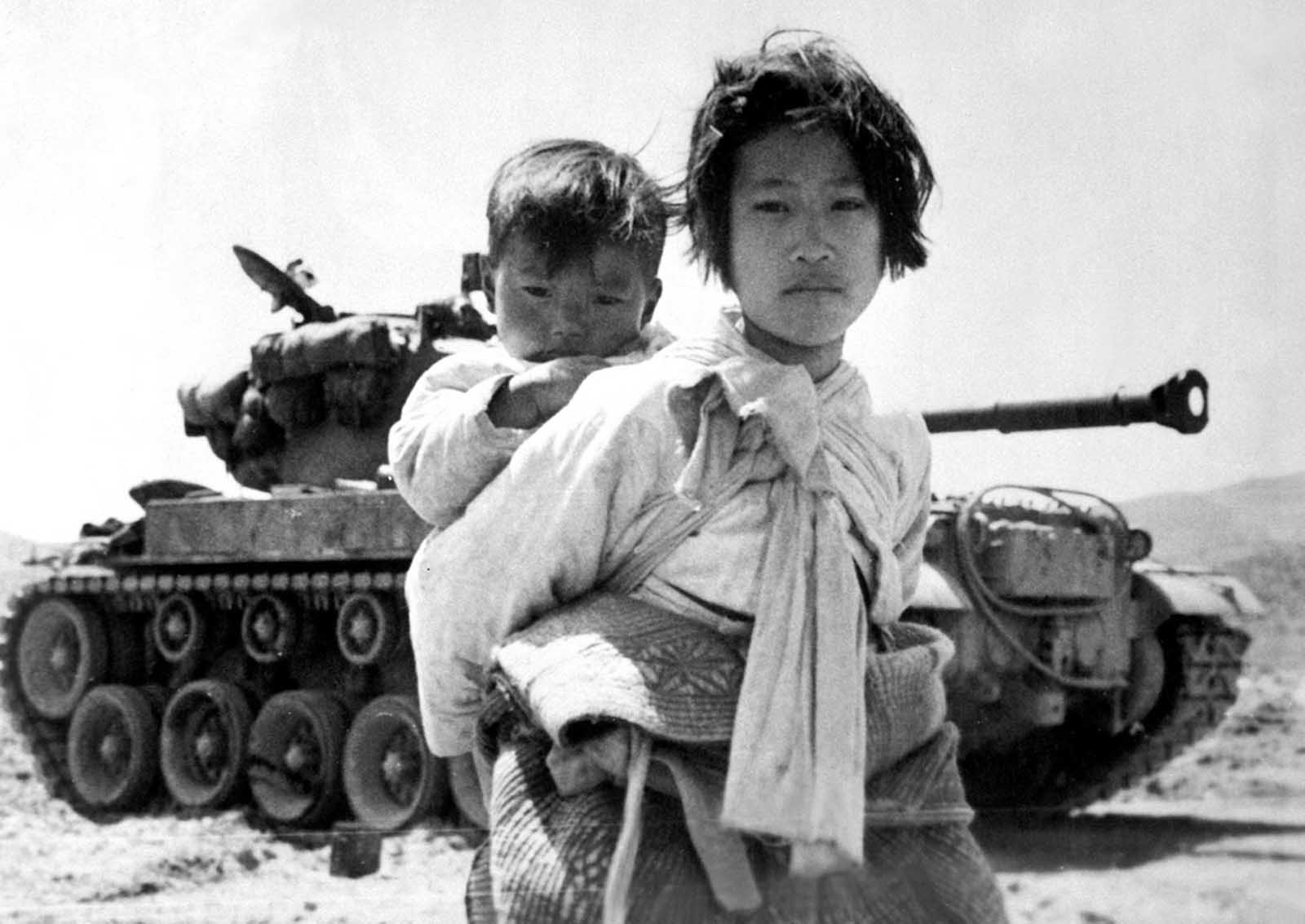 With her brother on her back, a war-weary Korean girl trudges by a stalled M-26 tank, at Haengju, Korea. on June 9, 1951.