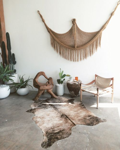 rustic interior with a large macrame, cacti and animal fur