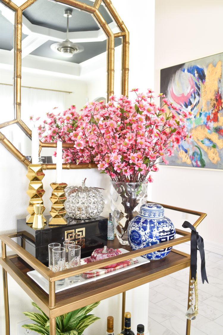 A gold bar cart is decorated for fall with chinoiserie decor, pink florals and pumpkins. | #pumpkindecor #falldecor #livingroomideas #monicawantsit