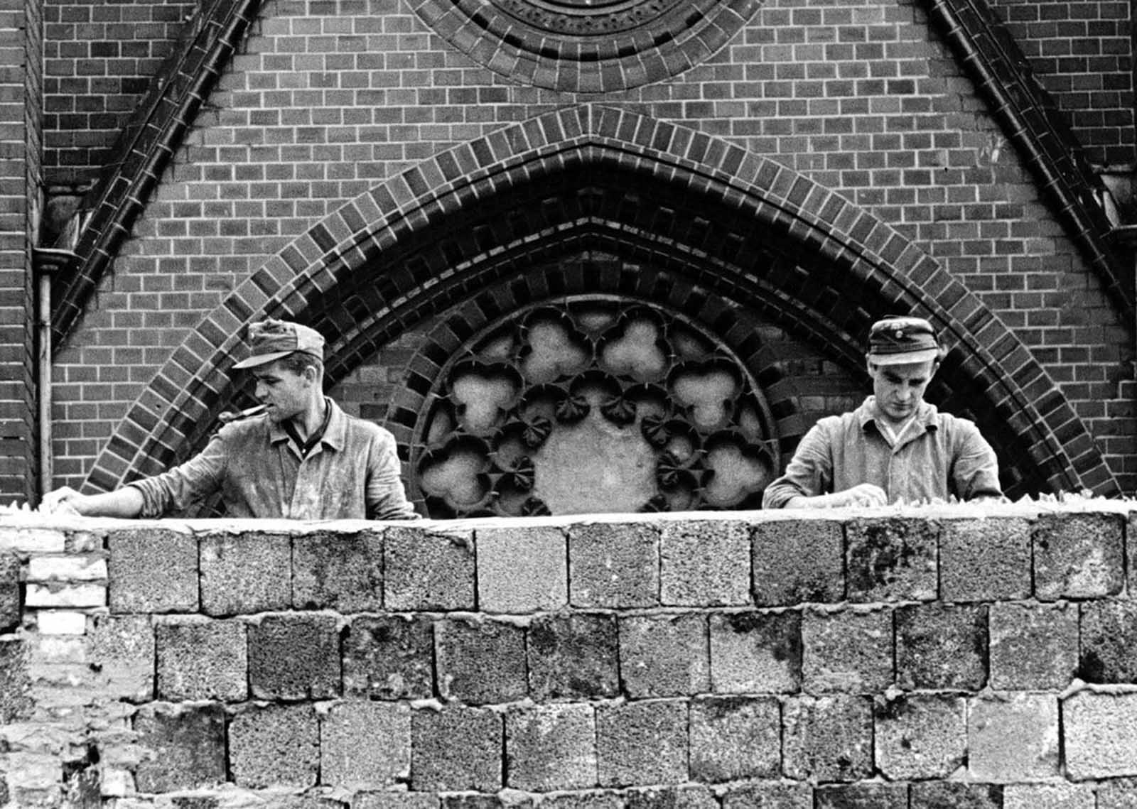 Blocking the church - Two East Germans work on a huge 15 foot wall, placing pieces of broken glass on the top to prevent East Berliners from escaping.