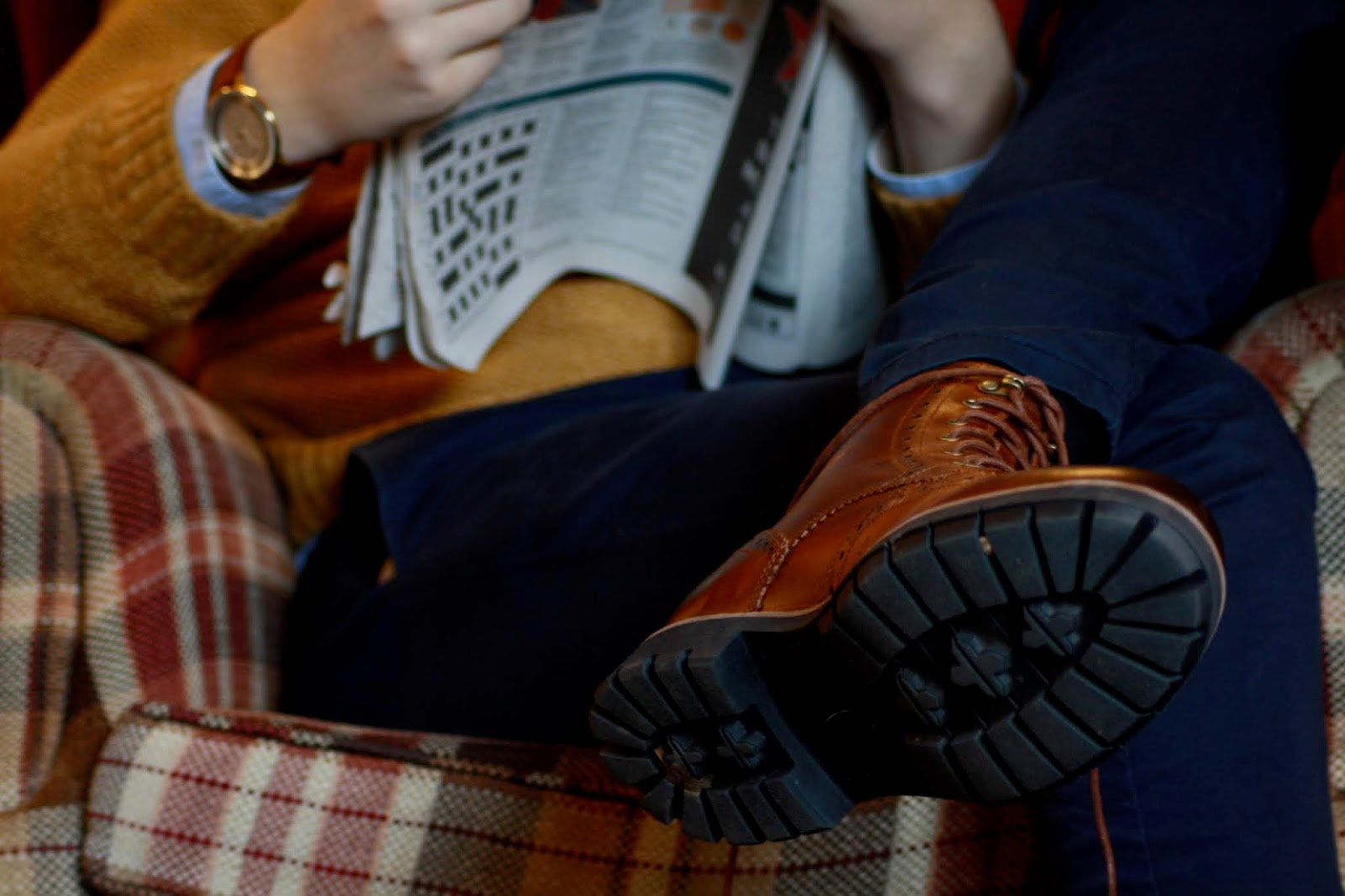 close up of a men's outfit comprising dark tan boots and watch, mustard jumper and blue trousers