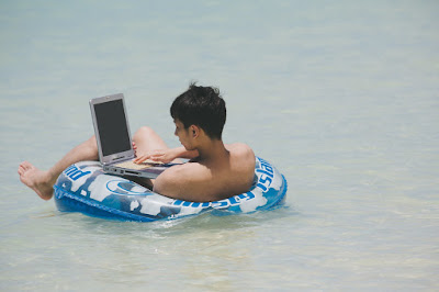 海でデジタル機器をいじる男性