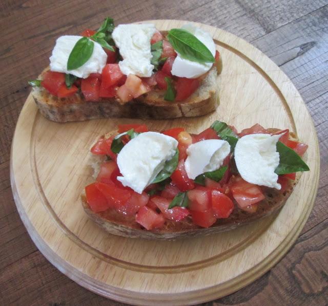 Taboa redonda de madeira servindo a bruschetta de tomate e mozzarella