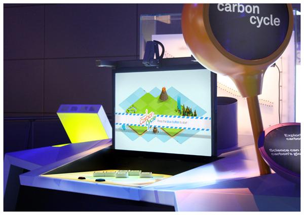 Imagem mostrando a bancada onde o projeto ficou exposto no museu. Uma mesa com prquenos blocos de madeira e uma tela na frente mostrando a ilha do visitante.