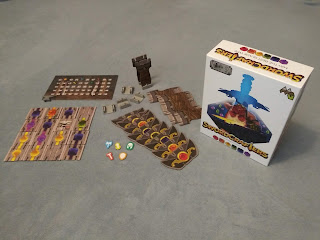 Most of the components of the game, next to the box. There is a score tracker with pieces for each player, a set of tiles representing a section of a sword blade, most with a single jewel in the centre, cardboard tiles shaped like sword hilts, plastic pommels into which those hilts can be inserted, allowing the sword to stand up, and some crossguard tiles.