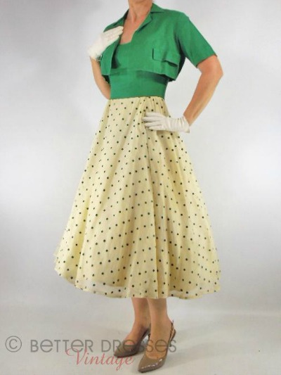 Model dressed in kelly green bolero jacket over dotted halter dress
