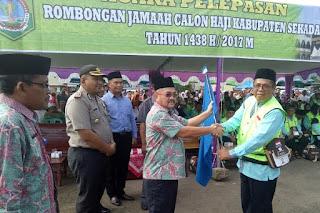 Wakil Bupati Sekadau Aloysius, SH.M.Si Serah bendera kepada ketua rombongan calon Haji Kabupaten Sekadau Zakaria Umar Arif Dalam Pelepasan Jamaah Haji