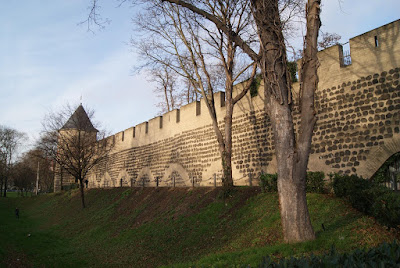 Eine alte Steinmauer mit einem Turm im Hintergrund