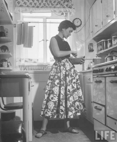 Nina Leen photograph of model Joan Wilson cooking in 1950's era kitchen