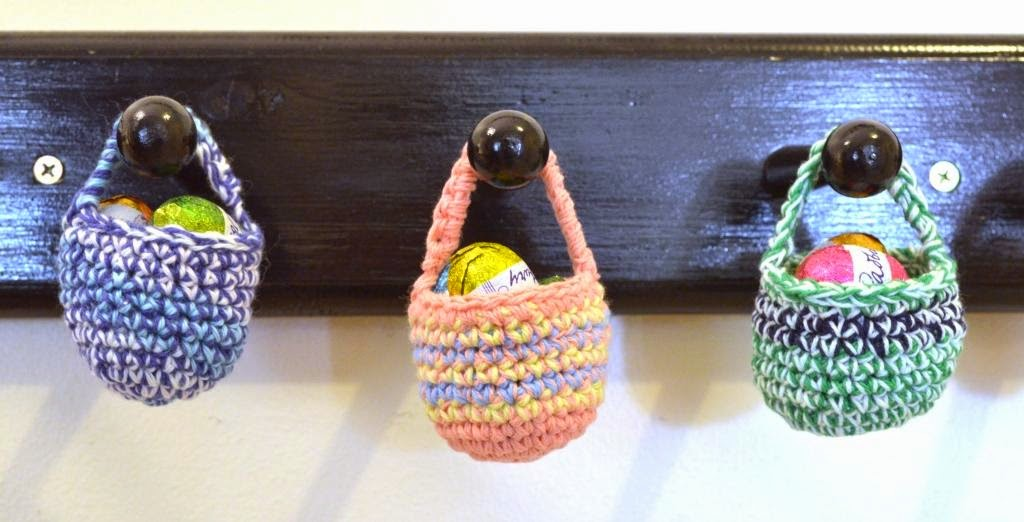 Three black wooden wall pegs in a horizontal wall; each peg has one mini basket hanging from it. The baskets contain 3–4 mini chocolate eggs each. From left to right: blue/aqua/white, apricot/yellow/light blue, green/navy/variegated mint