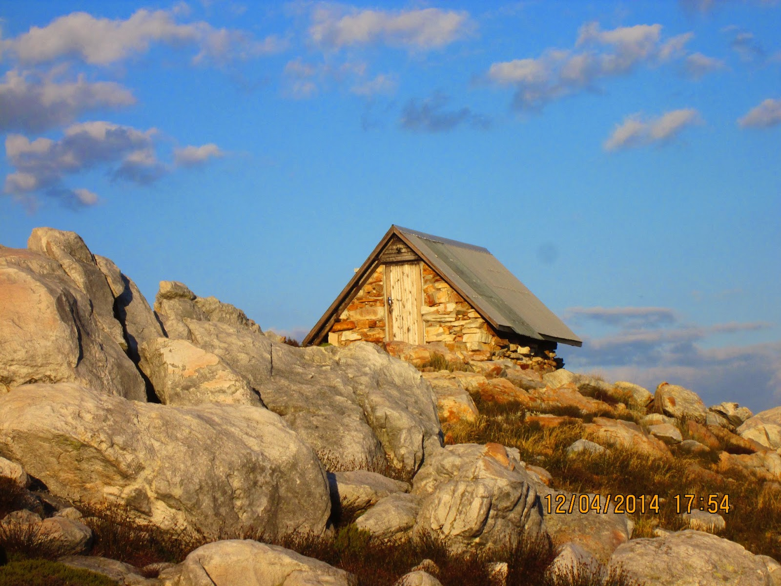 Hut on top of a mountain with rocks in front