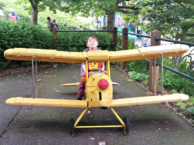Boy sitting on a Lego aeroplane at Legoland