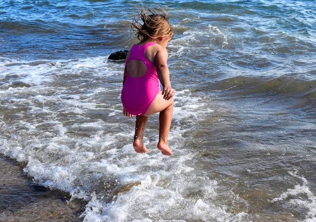 Girl jumps in the sea.